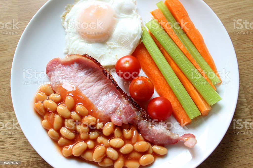 Low-calorie, healthy fried-breakfast, bacon, poached egg, carrots, celery, tomatoes, baked-beans royalty-free stock photo