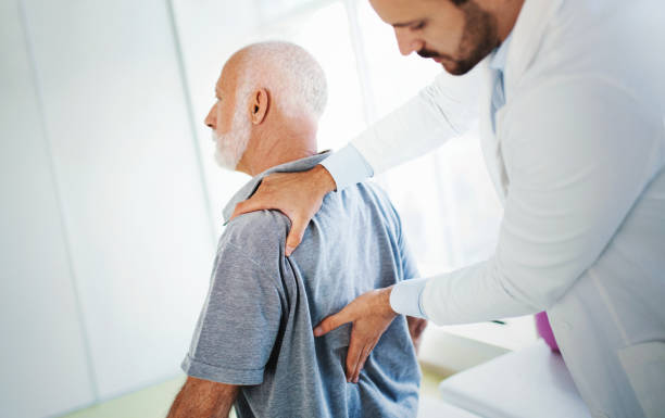 Lower back pain medical examination. Closeup side view of an early 60's senior gentleman having some lower back pain. He's at doctor's office having medical examination by a male doctor. The doctor is touching the sensitive area and trying to determine the cause of pain. back pain stock pictures, royalty-free photos & images