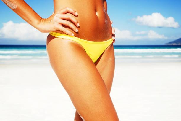 Lower half of a bikini clad woman on a tropical beach stock photo