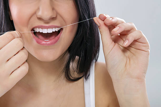 Lower half of face of woman smiling and flossing her teeth stock photo