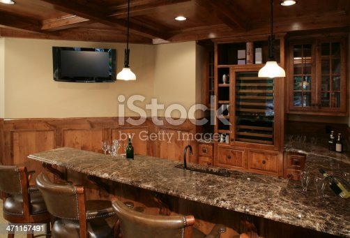 Lower level bar finished with granite counter tops, a wall mounted flat screen television and beautiful woodwork.