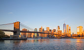 Lower Manhattan skyline and Brooklyn Bridge in New York City at sunrise