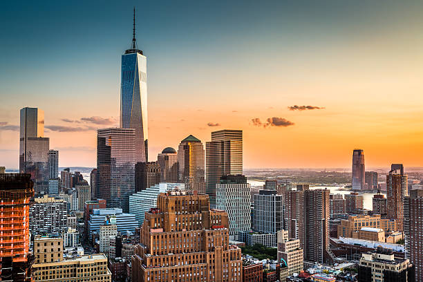 Lower Manhattan at sunset Lower Manhattan skyline at sunset with Freedom Tower standing tall above the skyline manhattan financial district stock pictures, royalty-free photos & images