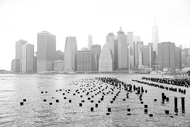 Lower Manhattan cityscape seen from Brooklyn Heights waterfront park, NYC Lower Manhattan cityscape seen from Brooklyn Heights waterfront park at New York City in a foggy day.  Black and white photo. south street seaport stock pictures, royalty-free photos & images