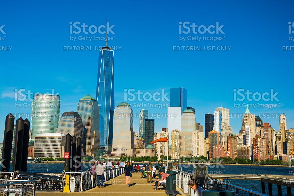 Lower Manhattan skyline and people waiting on a pier stock photo