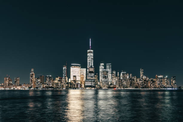 Lower Manhattan skyline, New York skyline at night Great night view of the famous skyline of Manhattan downtown district with many skyscrapers, whose lights reflects in the water. lower manhattan stock pictures, royalty-free photos & images