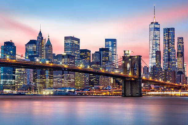Lower Manhattan skyline Brooklyn Bridge at and the Lower Manhattan skyline under a purple sunset new york state stock pictures, royalty-free photos & images