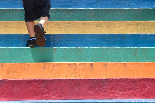 Lower part of a boy in casual shoe walking up outdoor colorful stair,children lifestyle successful concept stock photo