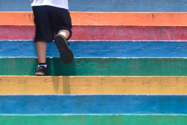 Lower part of a boy in casual shoe walking up outdoor colorful staircase,children lifestyle successful concept stock photo