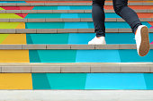 istock Lower part of teenage girl in casual shoe walking up outdoor colorful stair,teenage lifestyle successful concept 1145033939