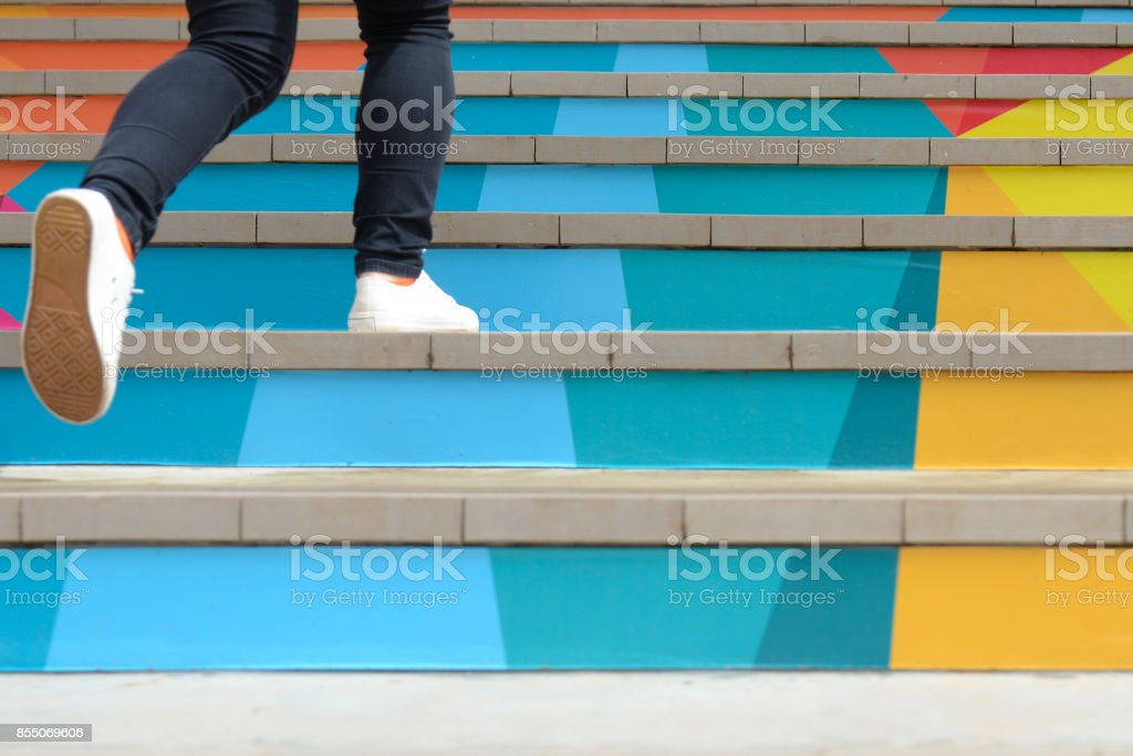 Lower part of teenage girl in casual shoe walking up outdoor colorful stair,teenage lifestyle successful concept royalty-free stock photo