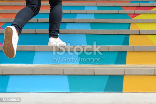 istock Lower part of teenage girl in casual shoe walking up outdoor colorful stair,teenage lifestyle successful concept 855069606