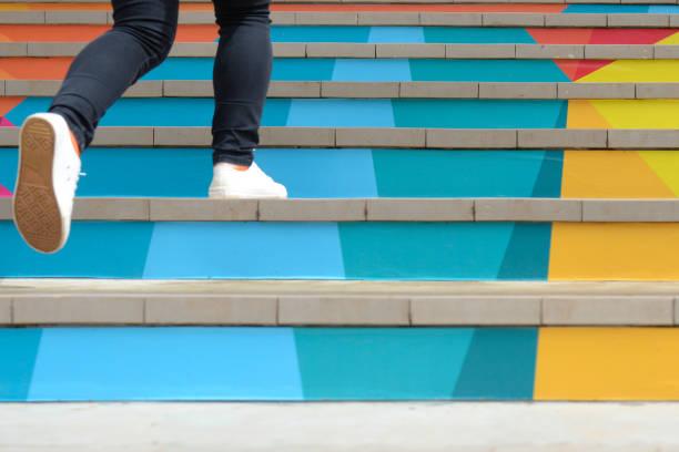 unteren teil des teenager-mädchen in freizeitschuh wandern outdoor-bunte treppe, teenage lebensstil erfolgskonzept - treppe stock-fotos und bilder