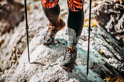 Carefully navigating rocky terrain in hiking boots, using walking sticks.