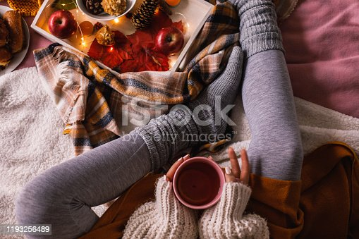 Directly above shot of unrecognizable young woman sitting in her cozy bed and enjoying a warm cup of tea on a cold autumn day.