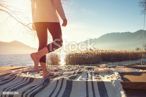 Lower section of woman standing on a boat above the lake, sunbeam on the skin.