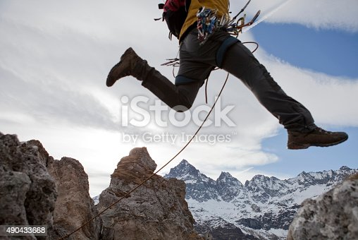 Lower torso of mountaineer in mid-air jump, Piedmont, Italy