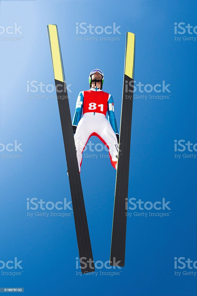 Lower View of Ski Jumper in Mid-air stock photo
