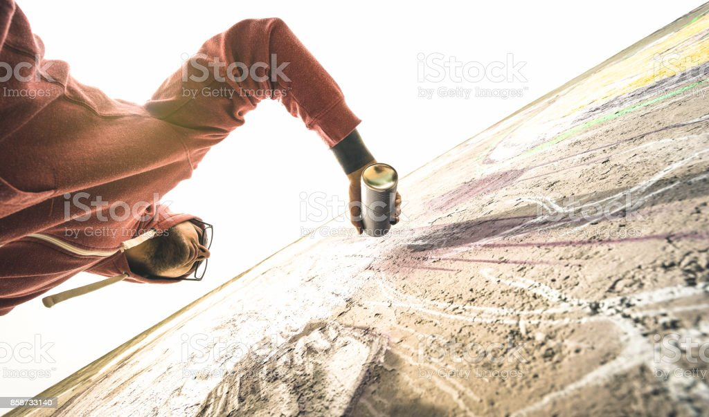 Lower view of street artist painting graffiti on generic wall - Modern art concept with urban guy performing and preparing live murales with green aerosol color spray - Warm retro backlight filter stock photo