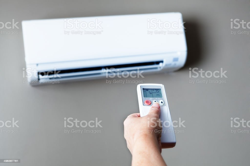 Lowering, Turning Off Air Conditioning to Conserve Electricity Energy Costs stock photo