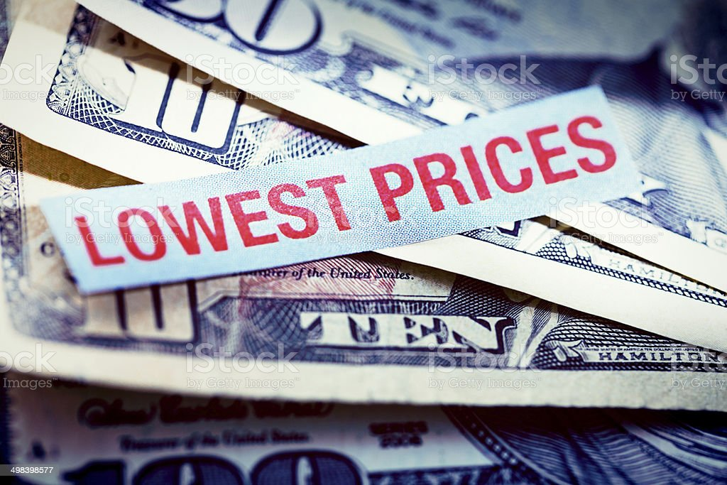 'lowest prices' says sign on stack of banknotes. Good news! stock photo
