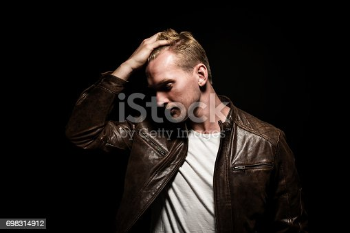 Handsome blonde man standing against a black background with a simple light above his head, wearing a brown leather jacket and white t-shirt.