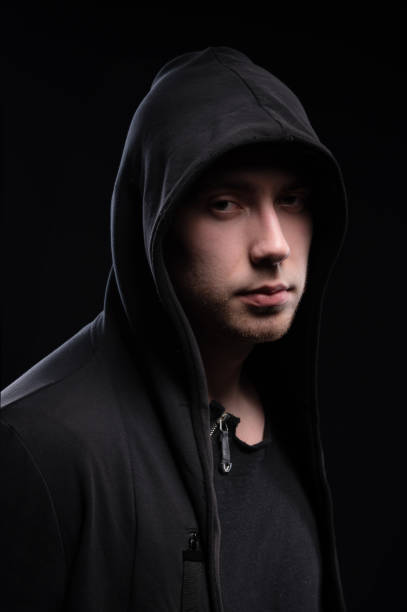 A low-key studio portrait of a large man in a hood sits pondering. Sex faces in the dark hacker stealth and anonymous surveillance hidden concept stock photo