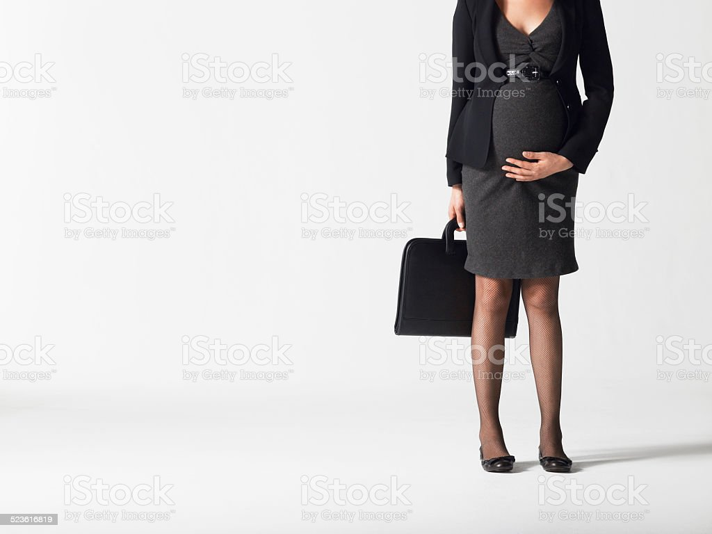 Lowsection Of Pregnant Businesswoman With Briefcase stock photo