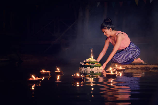 loy krathong traditional festival, thai woman hold kratong, thailand, asia woman in thai dress traditional hold kratong and bring krathong to float in loi kratong day of thailand. - kratong stock photos and pictures