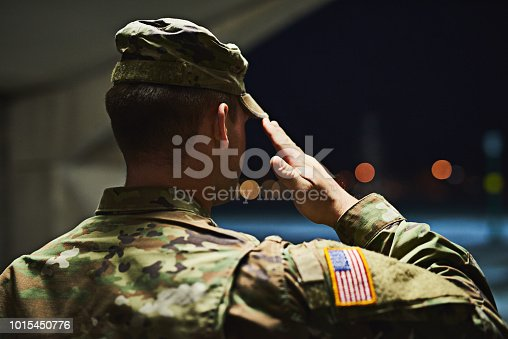 Rearview shot of a young soldier standing at a military academy and saluting