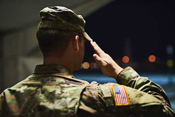 Loyal is the soldier who loves his country Rearview shot of a young soldier standing at a military academy and saluting insignia stock pictures, royalty-free photos & images