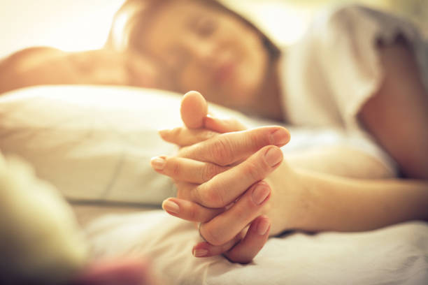 Loyalty is a lovely thing. Loyalty is a lovely thing. Young couple in bed. Focus is on hands. Space for copy. Close up. couple in bed stock pictures, royalty-free photos & images