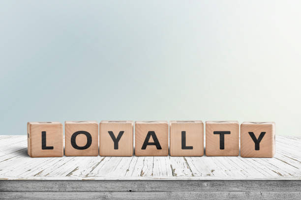 loyalty sign on a wooden table in bright daylight - fedeltà foto e immagini stock