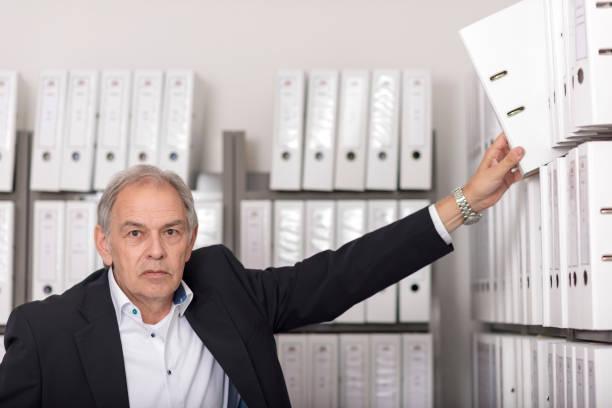 Älterer Mann mit weißem Hemd  stellt einen Dokumenten Ordner in ein Regal Älterer Mann mit weißem Hemd  stellt einen Dokumenten Ordner in ein Regal civil servant stock pictures, royalty-free photos & images