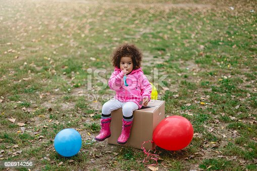 istock ltoddler girl sitting on a box and blowing party horn 626914256