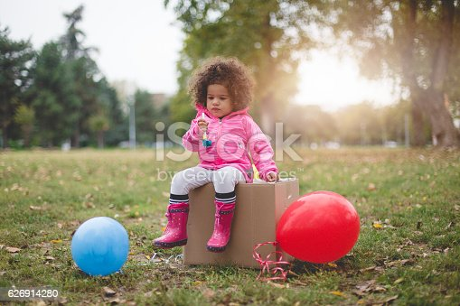 istock ltoddler girl sitting on a box and blowing party horn 626914280