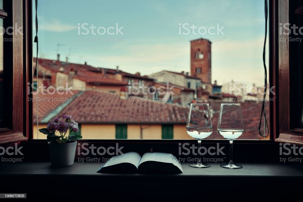 Lucca window view with wine book flower stock photo