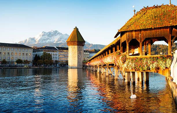 lucerne switzerland reuss chapel bridge at dawn with mount pilatus - lucerne stock pictures, royalty-free photos & images