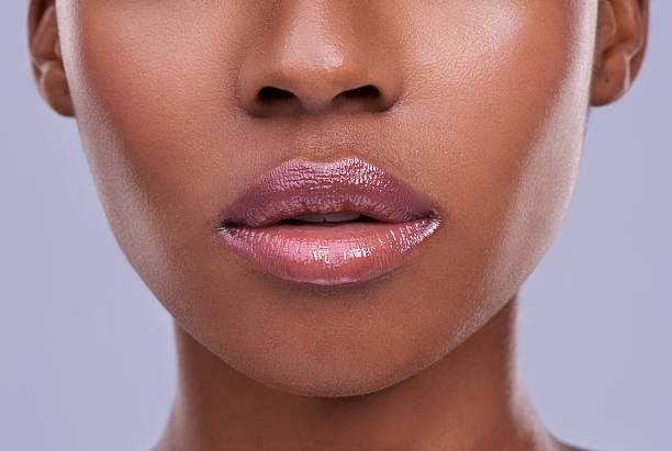 Lucious lips Cropped shot of a young woman's mouth against a purple background human lips stock pictures, royalty-free photos & images