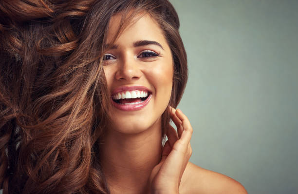 Lucious locks and happy laughter Studio portrait of a beautiful woman with long locks posing against a grey background long hair stock pictures, royalty-free photos & images