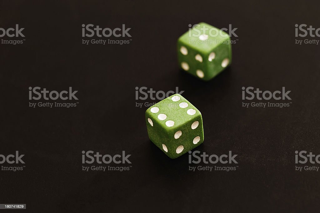 Lucky 7 but unlucky green; two dice on black background royalty-free stock photo