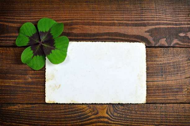 lucky clover and blank greeting card on wooden background - luck of the irish stock photos and pictures