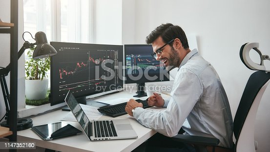 istock Lucky day. Happy young businessman or trader in formalwear and eyeglasses using laptop and smiling while sitting in his modern office 1147352160