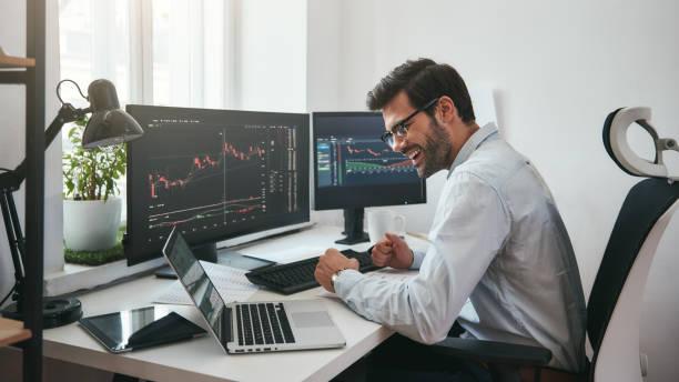 幸運な日だ天才的の幸せな若いビジネスマンやトレーダーは、彼の現代のオフィスに座っている間ノートパソコンと笑顔を使用して、眼鏡 - 投資家 ストックフォトと画像