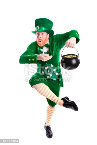 Full length photograph of a leprechaun holding gold in his hand and in his pot; he's dancing a jig; copy space