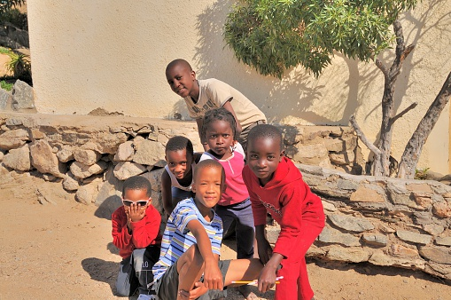 Luderitz, Namibia - May 9, 2012: A group of children escorted by an older brother stop to pose and mug for the camera and enjoy the interaction in Luderitz, Namibia in mid-afternoon.