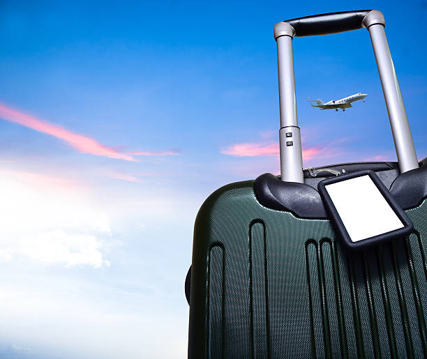 luggage and airplane on beautiful sky travel concept Bon Voyage; blank luggage tag on rolling carry-on suitcase with a beautiful blue sky backdrop and flying aircraft within the luggage pull-out handle. nice space for text. Logo or symbol can be placed on white blank tag space.  carry on luggage stock pictures, royalty-free photos & images