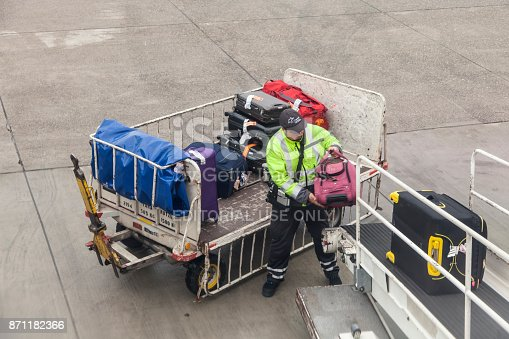 Frankfurt, Germany - Oct 10, 2017: Luggage being loaded from the trolley to belt conveyor and into the aircraft