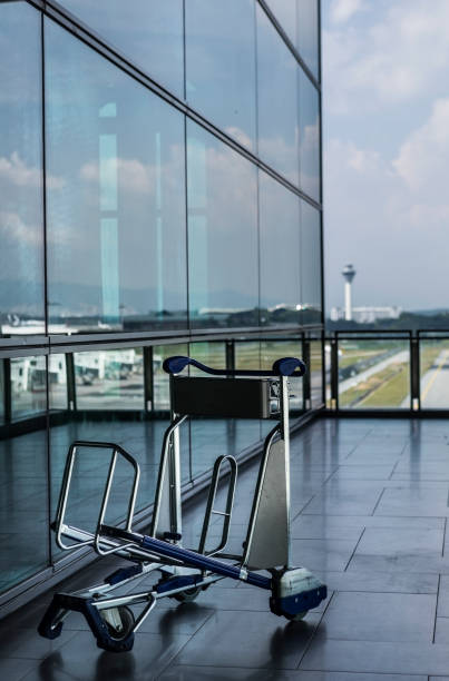 Luggage cart at a modern airport in Asia In a modern outdoor corridor of an international airport, an empty luggage cart stands by itself with glass window reflection behind and an airport traffic control tower in the background. kuala lumpur airport stock pictures, royalty-free photos & images