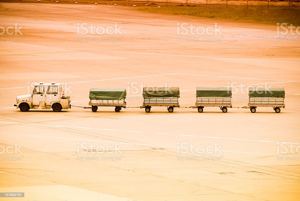 Luggage carts on airport runway at sunset, copy space royalty-free stock photo